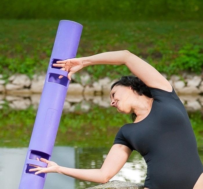 žena u řeky cvičí s fialovým rollerem