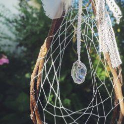 Detail talismanu s krystalem aqua aura v bílé síti